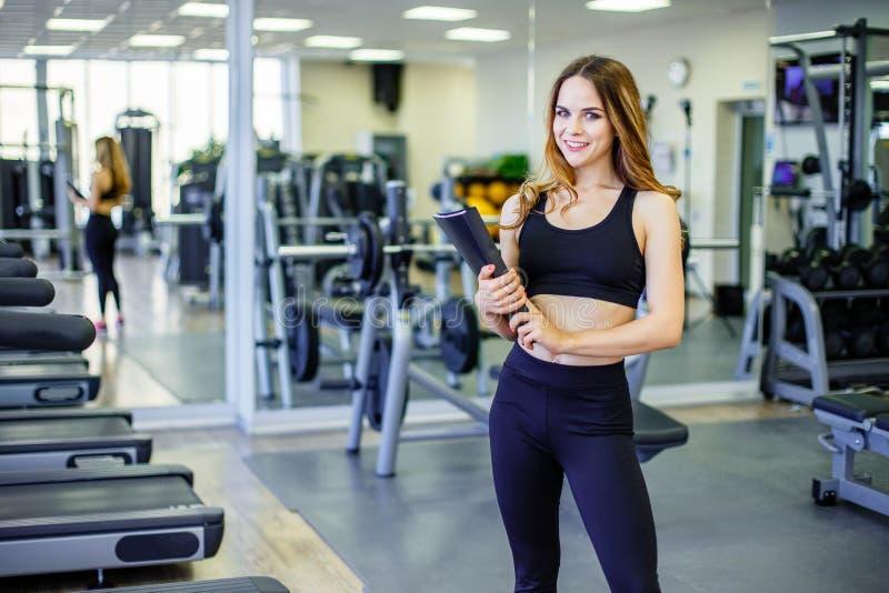 Mujer personal del instructor que sostiene el tablero con plan de entrenamiento en gimnasio foto de archivo