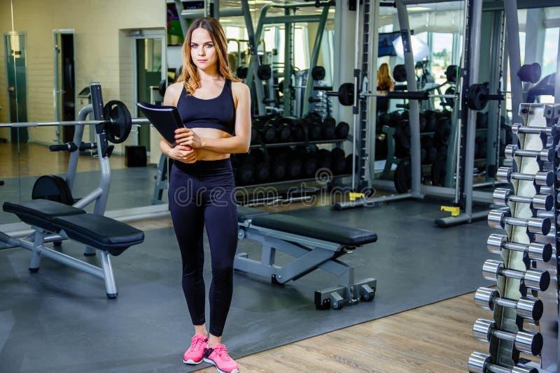 Mujer personal del instructor que sostiene el tablero con plan de entrenamiento en gimnasio fotos de archivo libres de regalías