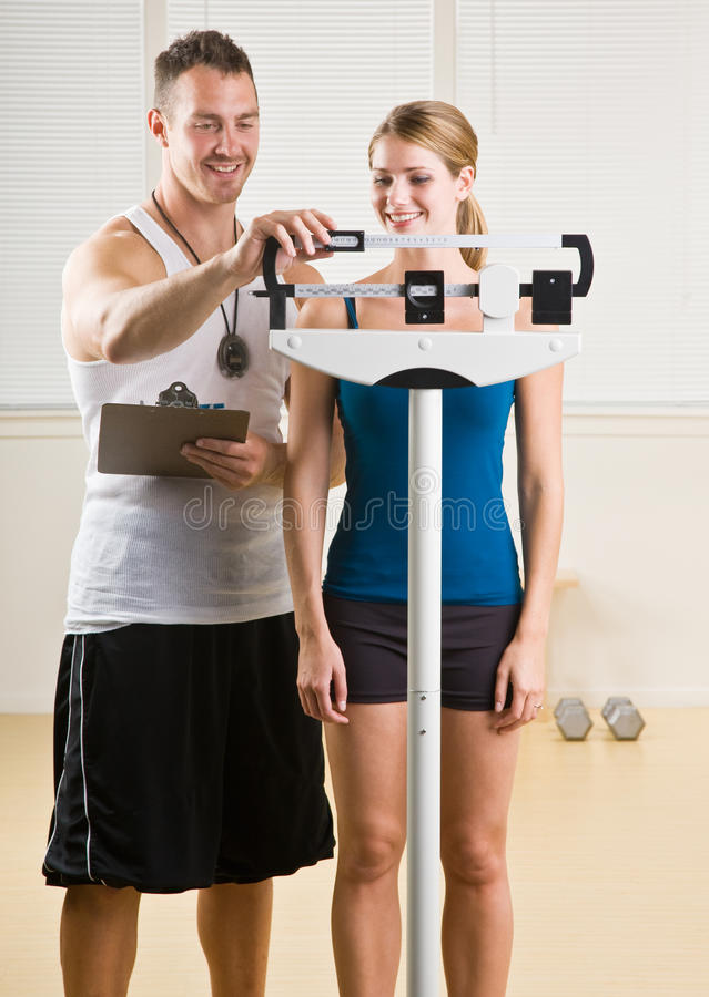 Mujer personal del peso del entrenamiento en club de salud imagenes de archivo