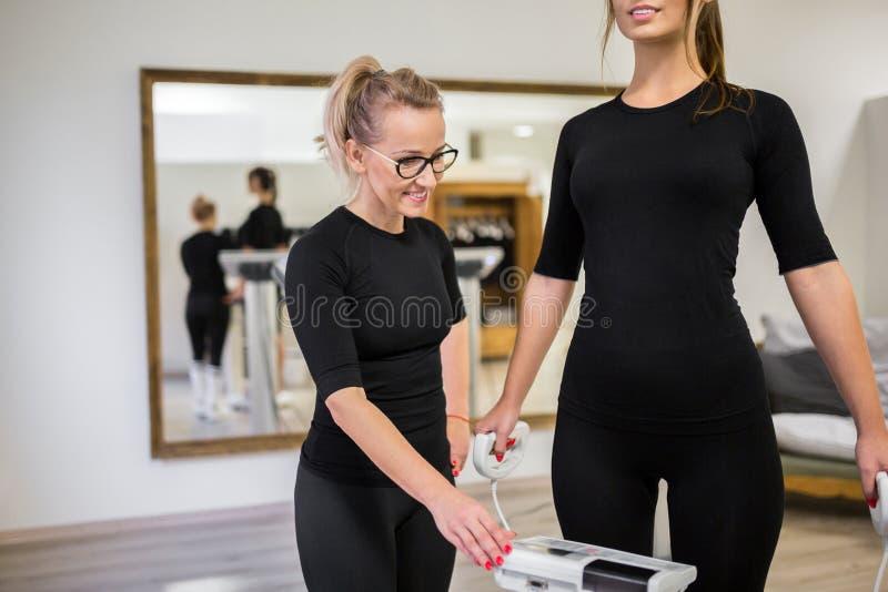 Mujer personal feliz del entrenamiento del instructor en la máquina del ccsme foto de archivo