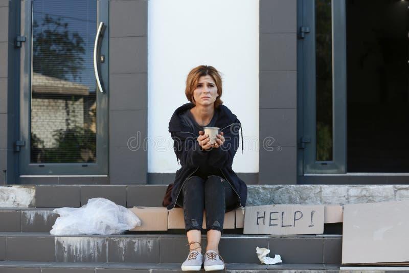 Mujer pobre con la taza que pide y que pide ayuda foto de archivo libre de regalías