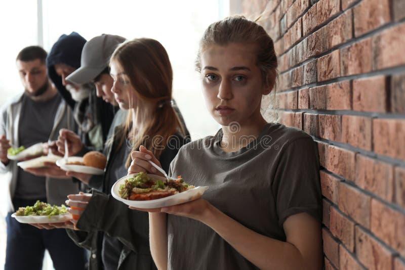 Mujer pobre joven y otras personas con la comida en la pared de ladrillo imágenes de archivo libres de regalías