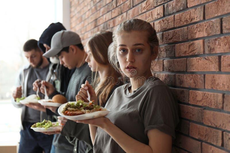 Mujer pobre joven y otras personas con la comida en la pared de ladrillo imagen de archivo libre de regalías