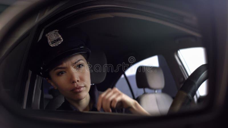 Mujer policía asiática que mira el espejo de coche, situación aventurada de observación, patrullando imagen de archivo libre de regalías