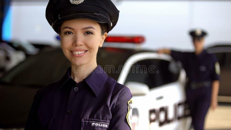 Mujer policía asiática sonriente que presenta a la cámara contra socio cerca del coche patrulla, deber fotos de archivo libres de regalías