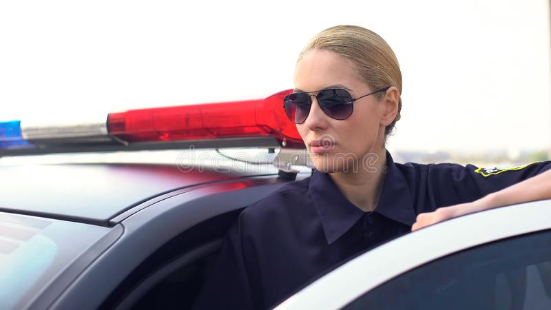 Mujer policía seria en las gafas de sol que controlan seguridad en el camino, colocándose cerca del coche imagen de archivo libre de regalías