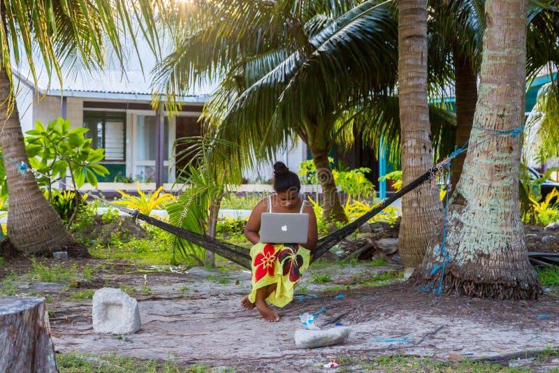 Mujer polinesia joven en una hamaca con un funcionamiento del cuaderno al aire libre debajo de las palmeras Tuvalu, Polinesia, oc imagen de archivo libre de regalías
