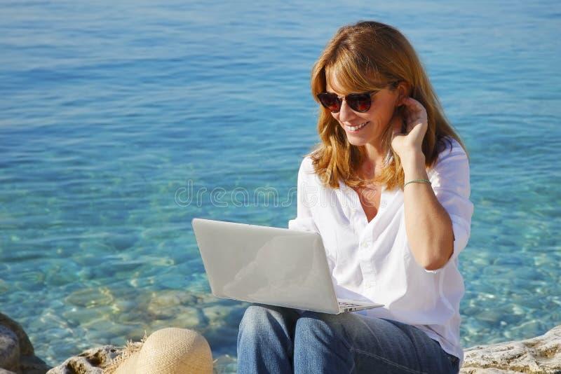 Mujer por el mar con el ordenador portátil imagen de archivo