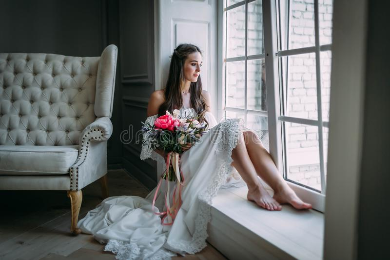 Mujer por la ventana Novia que mira hacia fuera la ventana, ella espera al novio fotos de archivo libres de regalías