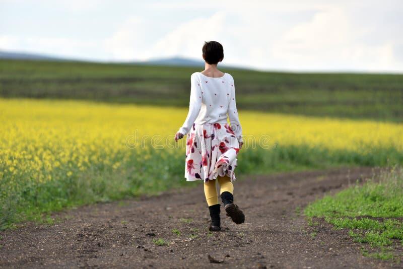 Mujer positiva alegre que corre en un camino del campo fotografía de archivo libre de regalías