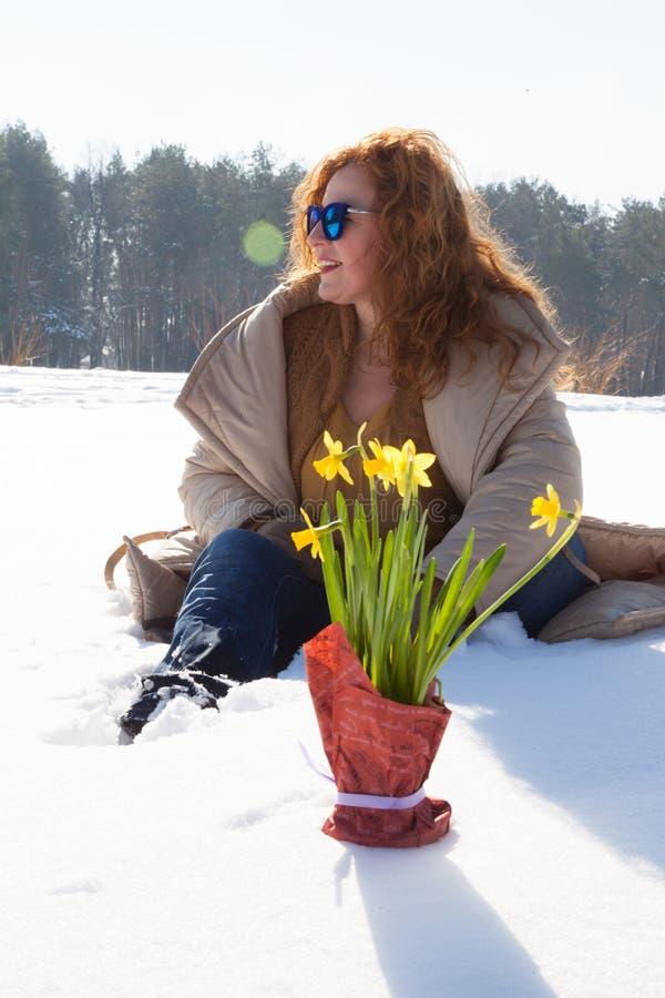 Mujer positiva atractiva que evita su vistazo mientras que se sienta en nieve acumulada por la ventisca imagen de archivo