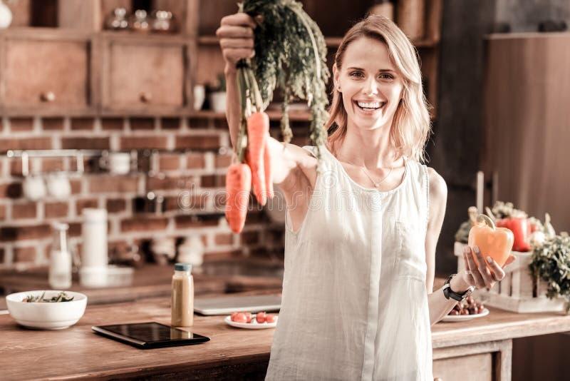 Mujer positiva encantada que sostiene zanahorias foto de archivo libre de regalías