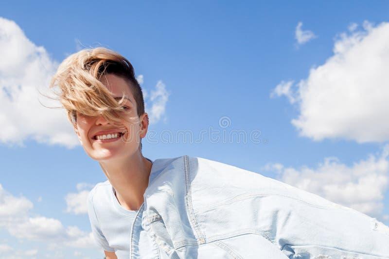 Mujer positiva joven con corte de pelo corto en chaqueta del dril de algodón con hai foto de archivo