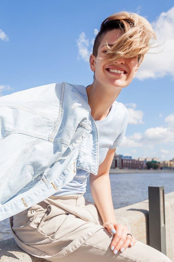 Mujer positiva joven con corte de pelo corto en chaqueta del dril de algodón con hai fotos de archivo libres de regalías