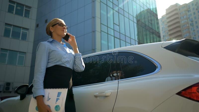 Mujer positiva que habla en el teléfono, principio del día del trabajo, señora acertada del negocio foto de archivo