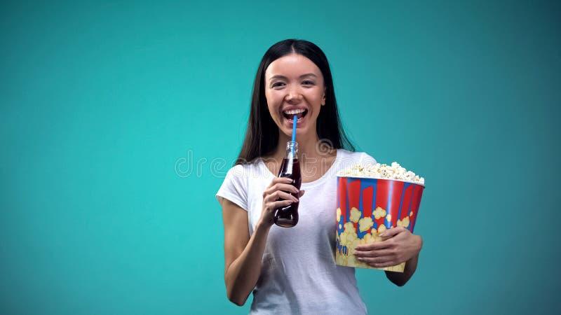 Mujer positiva que sostiene las palomitas y que bebe la soda, riéndose de comedia divertida foto de archivo libre de regalías