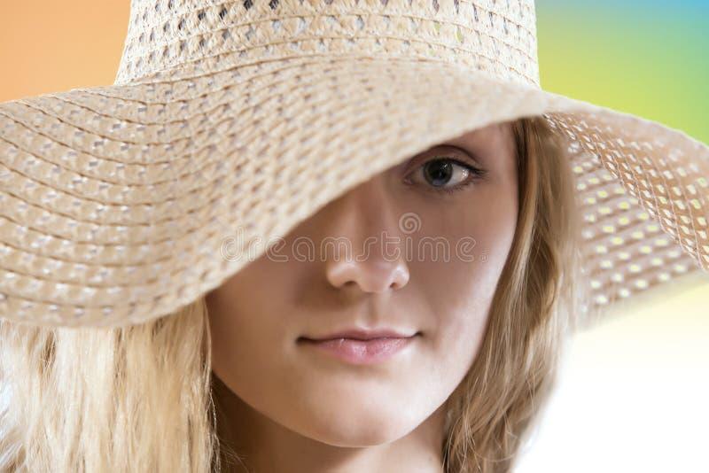 Mujer preciosa con cierre del sombrero del verano de la paja encima del retrato imagen de archivo