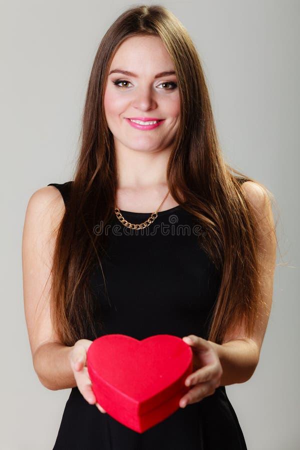 Mujer preciosa con la caja de regalo en forma de corazón roja imagenes de archivo