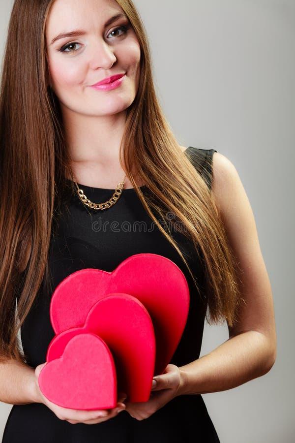 Mujer preciosa con las cajas de regalo en forma de corazón rojas imagenes de archivo