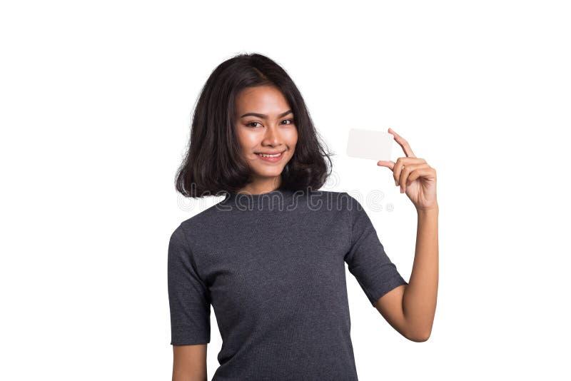 Mujer preciosa de Asia con la tarjeta de visita en el fondo blanco imagenes de archivo