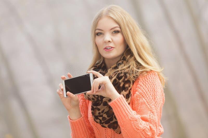 Mujer preciosa de la moda en el parque que toma la foto del selfie imagenes de archivo