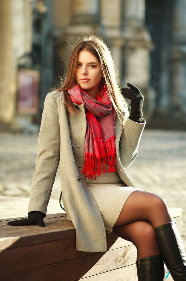 Mujer preciosa en la capa que se sienta en la calle de la ciudad en luz del sol fotografía de archivo libre de regalías