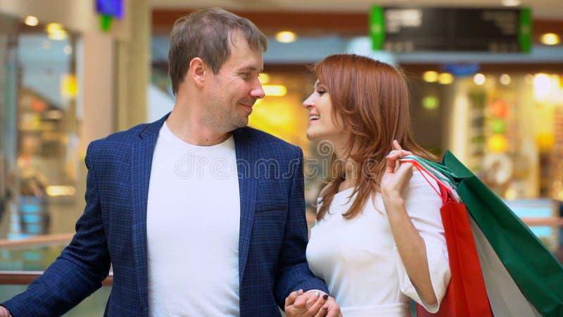Mujer preciosa que disfruta de hacer compras en la alameda con su novio fotografía de archivo