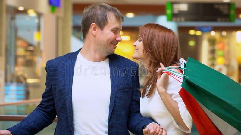 Mujer preciosa que disfruta de hacer compras en la alameda con su novio imagenes de archivo