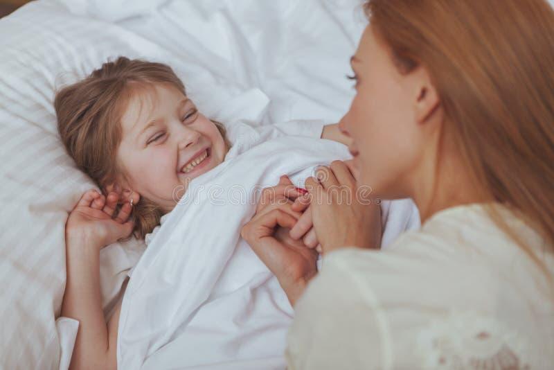 Mujer preciosa que mira su dormir de la hija imagen de archivo libre de regalías