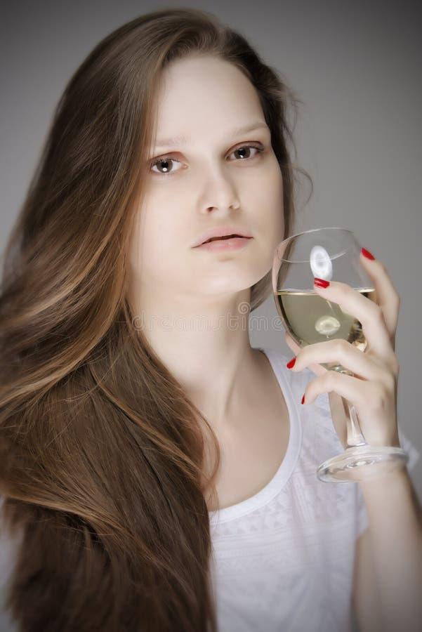 Mujer preciosa que prueba el vino blanco foto de archivo