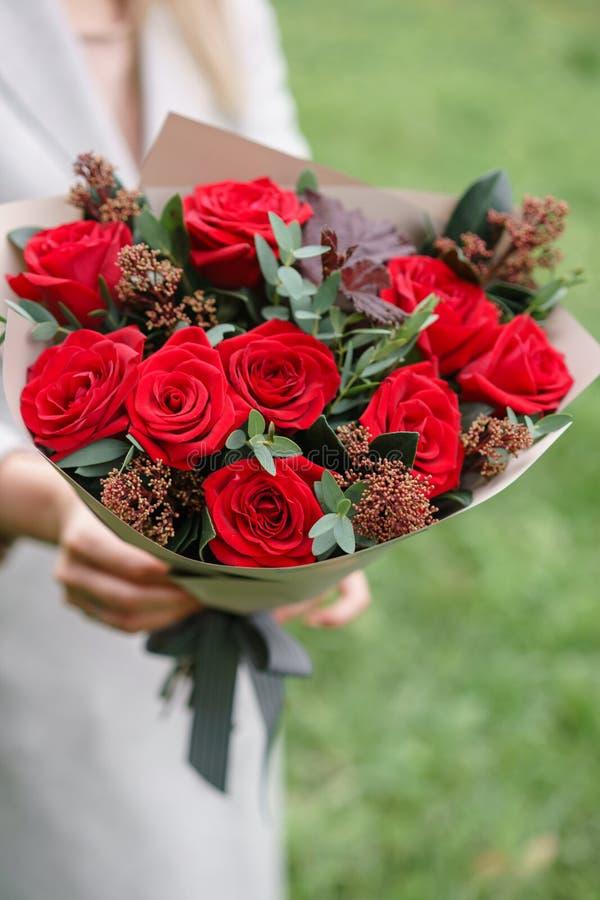 Mujer preciosa que sostiene un ramo hermoso del otoño centro de flores con los claveles y las rosas rojas del jardín Rosa del col imagen de archivo
