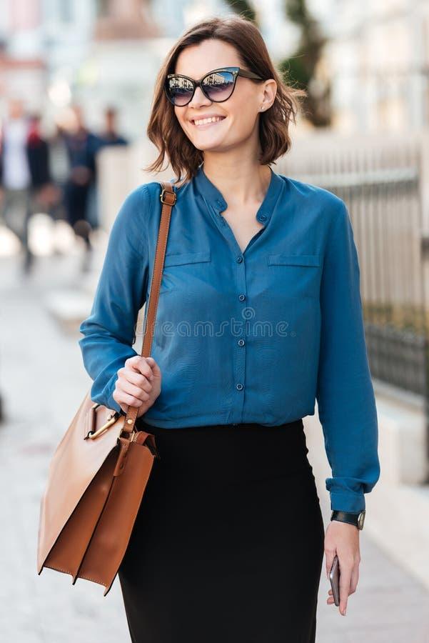 Mujer preciosa sonriente en gafas de sol en una calle imágenes de archivo libres de regalías