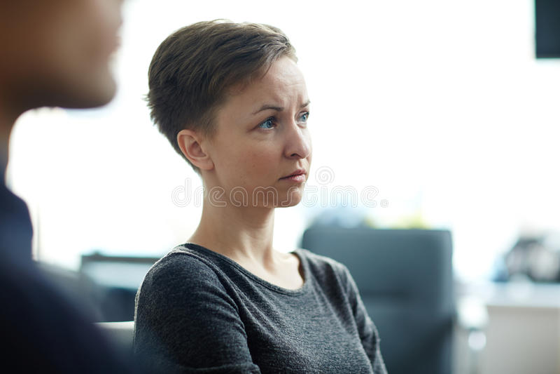 Mujer preocupada jóvenes que escucha en el seminario fotos de archivo