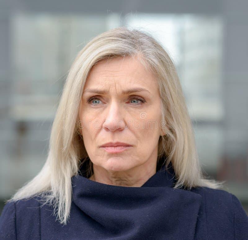 Mujer preocupada que mira para arriba con un ceño fruncido imagenes de archivo