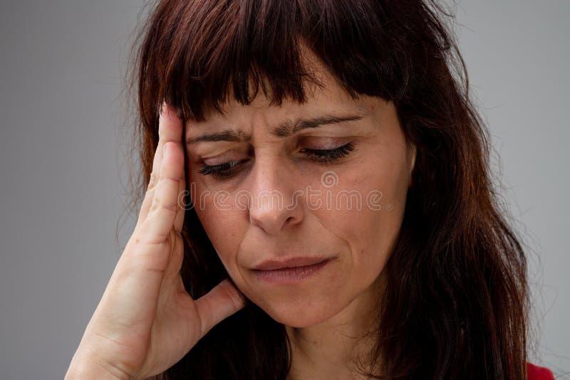 Mujer preocupante con su mano a su cabeza fotos de archivo