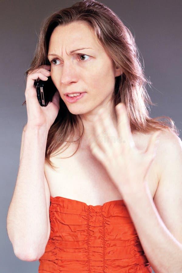 mujer preocupante en con clase joven hermoso del teléfono celular en vestido de cóctel imagen de archivo