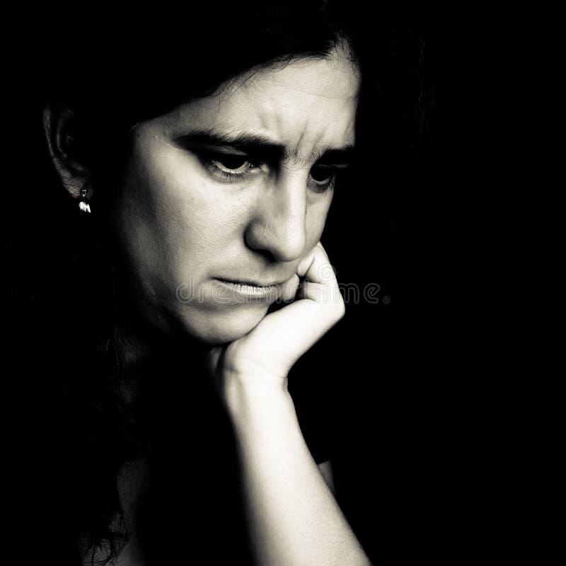 Mujer preocupante en un fondo negro imagen de archivo