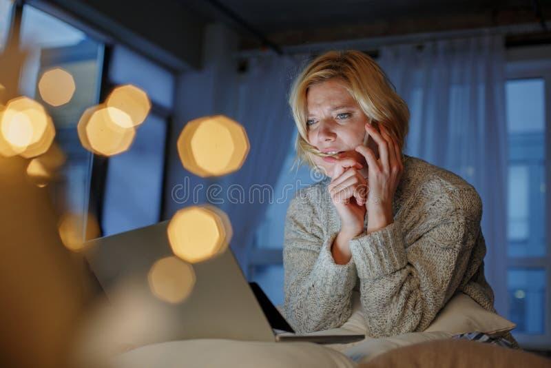 Mujer preocupante que charla en el teléfono en casa fotografía de archivo libre de regalías