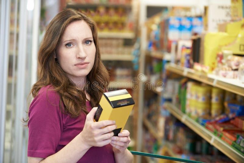 Mujer preocupante que comprueba el etiquetado de alimentos en la caja en supermercado fotos de archivo