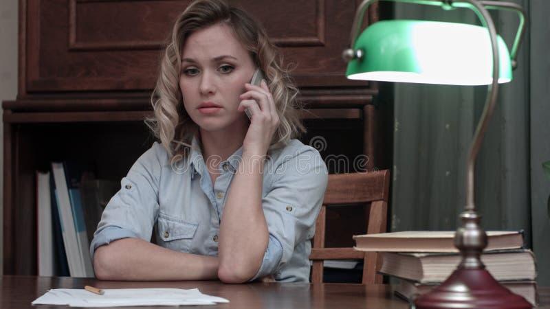 Mujer preocupante que contesta a una llamada de teléfono con malas noticias y que toma su cabeza en manos foto de archivo