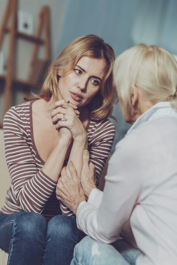 Mujer preocupante que habla con la madre imagenes de archivo