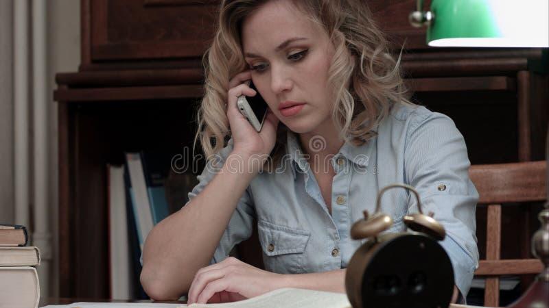 Mujer preocupante que habla en el teléfono que se sienta en su lugar de trabajo fotografía de archivo libre de regalías