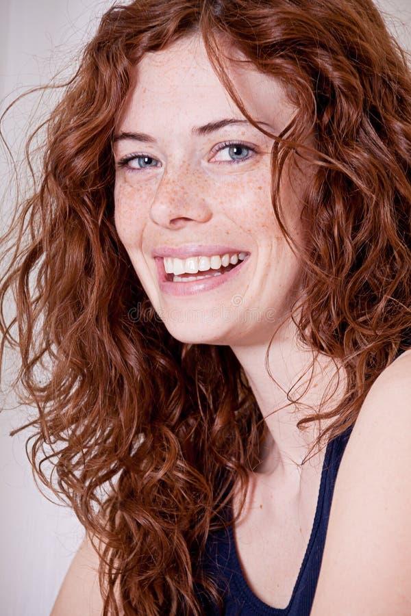 Mujer principal roja hermosa con la sonrisa de la peca foto de archivo libre de regalías