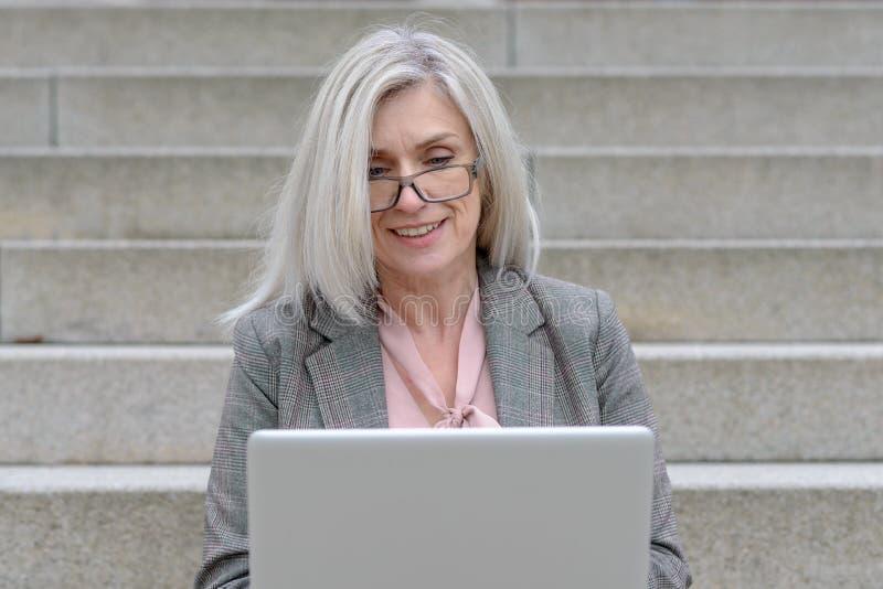 Mujer profesional atractiva usando un ordenador portátil fotos de archivo