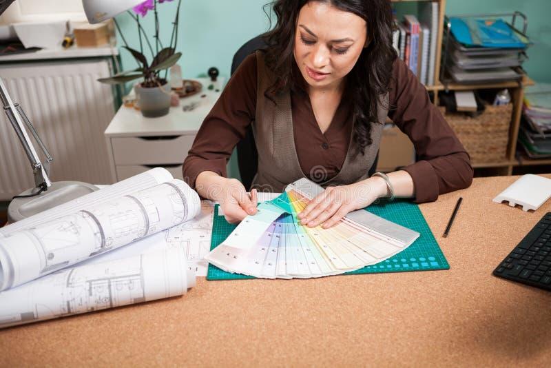 Mujer profesional del arquitecto en su oficina con las tarjetas del color en f imagen de archivo