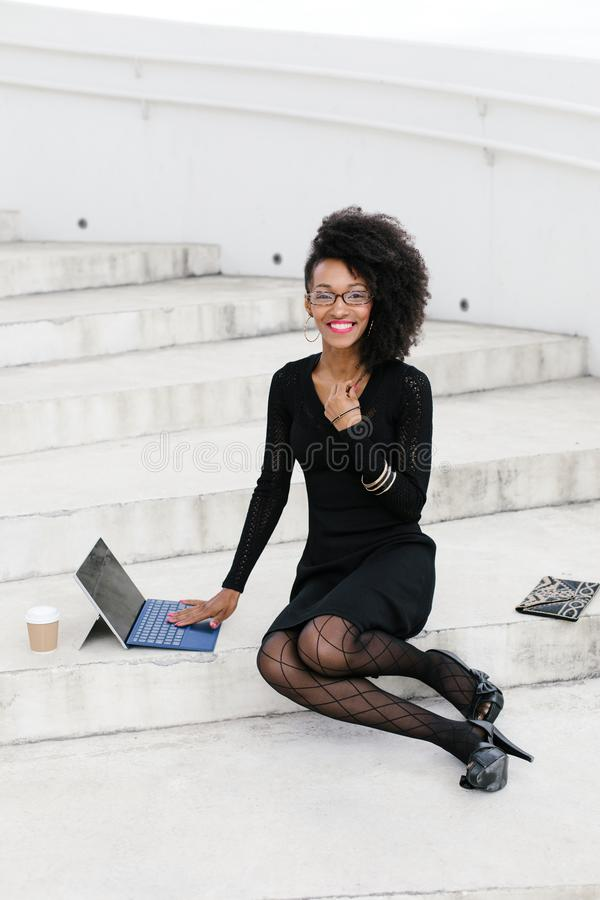 Mujer profesional del peinado afro joven elegante usando la tableta fotografía de archivo