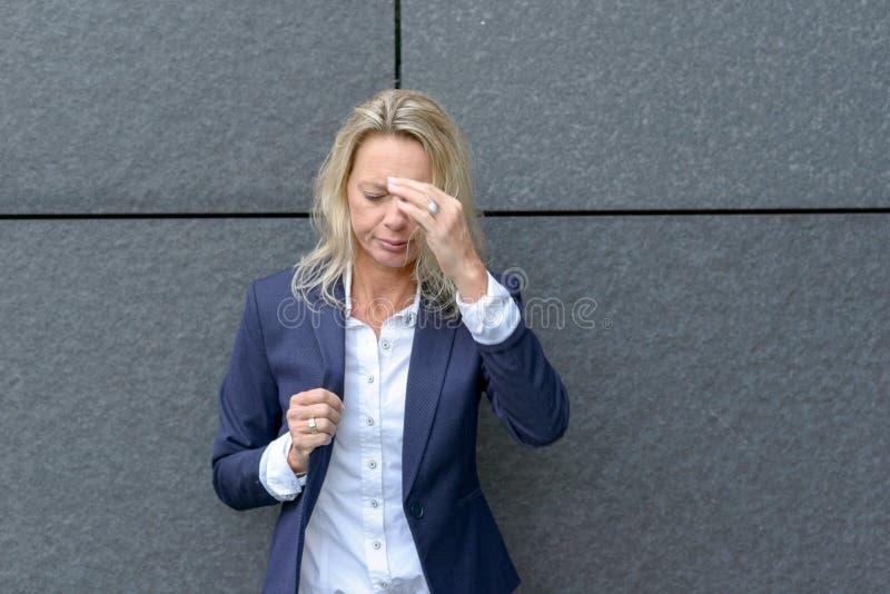 Mujer profesional elegante que sufre un dolor de cabeza fotografía de archivo