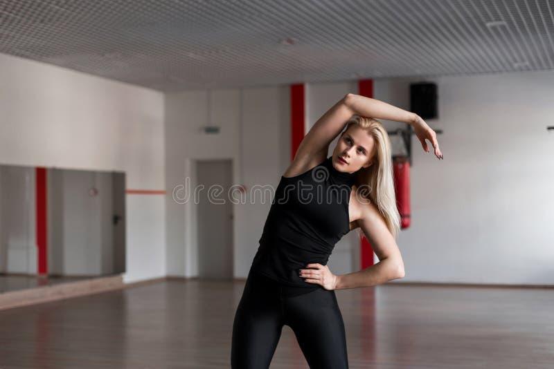Mujer profesional joven del instructor en la ropa de deportes negra dedicada a un estudio de la aptitud Muchacha hermosa en el en imagen de archivo libre de regalías
