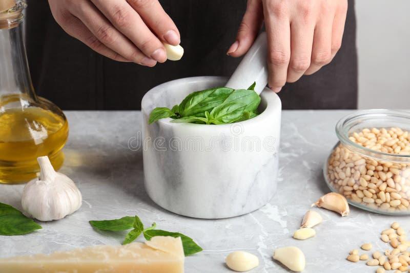 Mujer que añade el ajo en el mortero con la salsa del pesto en la tabla imagen de archivo libre de regalías