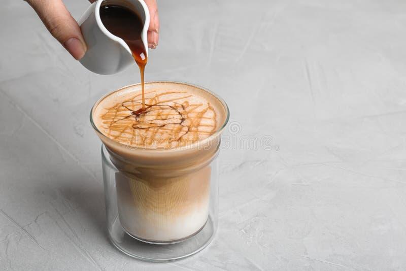 Mujer que añade el jarabe del caramelo al macchiato del latte en la tabla imágenes de archivo libres de regalías